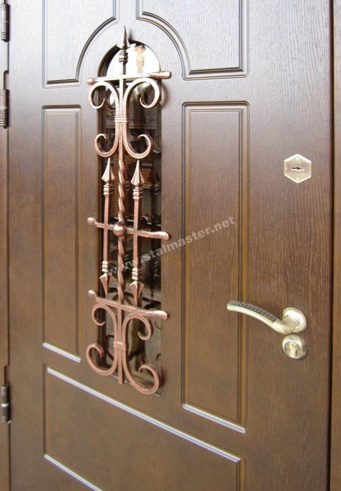 железная дверь с кованой отделкой